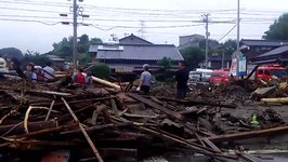 Tree Branches and Debris Strewn Across Asakura Streets Following Flooding