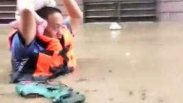 Police Officer Carries Baby Overhead in Chest-High Chinese Floodwater