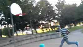A teen boy slips and falls on a bucket while dunking basketball outdoors